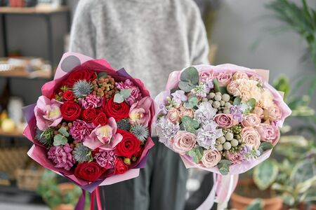 European floral shop. Two Beautiful bouquets of mixed flowers in womans hands. the work of the florist at a flower shop. Delivery fresh cut flower Stockfoto - 134593097