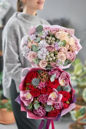 European floral shop. Two Beautiful bouquets of mixed flowers in womans hands. the work of the florist at a flower shop. Delivery fresh cut flower Stockfoto - 134593101