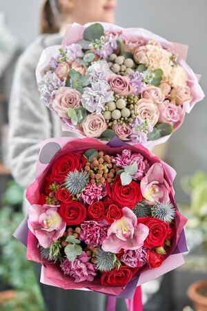 European floral shop. Two Beautiful bouquets of mixed flowers in womans hands. the work of the florist at a flower shop. Delivery fresh cut flower Stockfoto - 134593102