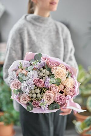 Modern floral shop. Finished work of the florist. Cute bouquet of mixed flowers in womans hands. Delivery fresh cut flower Stockfoto - 134593103