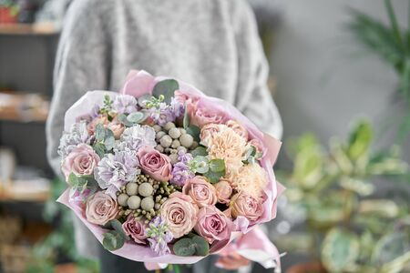 Modern floral shop. Finished work of the florist. Cute bouquet of mixed flowers in womans hands. Delivery fresh cut flower Stockfoto - 134593105
