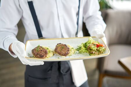 The waiter is holding a plate Delicious juicy meat cutlets, mashed potatoes sprinkled with greens and fresh healthy salad of tomatoes and lettuce leaves. Stockfoto - 134593107