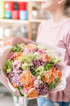 European floral shop. Beautiful bouquet of mixed flowers in womans hands. the work of the florist at a flower shop. Delivery fresh cut flower Stockfoto - 134593108