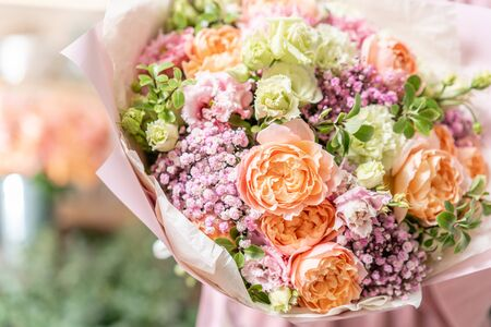 European floral shop. Beautiful bouquet of mixed flowers in womans hands. the work of the florist at a flower shop. Delivery fresh cut flower Stockfoto - 134593109
