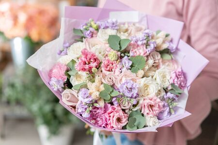 European floral shop. Beautiful bouquet of mixed flowers in womans hands. the work of the florist at a flower shop. Delivery fresh cut flower Stockfoto - 134593113