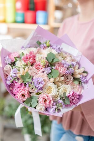 European floral shop. Beautiful bouquet of mixed flowers in womans hands. the work of the florist at a flower shop. Delivery fresh cut flower Stockfoto - 134593116