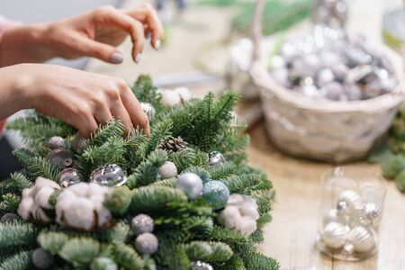 A woman decorates a Christmas arrangement. Hands close-up. Master class on making decorative ornaments. Christmas decor with their own hands. The new year celebration. Flower shop Stockfoto - 134593121