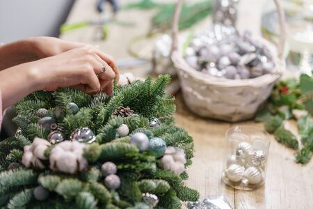 A woman decorates a Christmas arrangement. Hands close-up. Master class on making decorative ornaments. Christmas decor with their own hands. The new year celebration. Flower shop Stockfoto - 134593119
