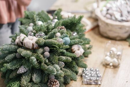 Christmas decor with their own hands. Master class on making decorative ornaments. Flower shop. Woman created a xmas arrangement. Stockfoto - 134593127