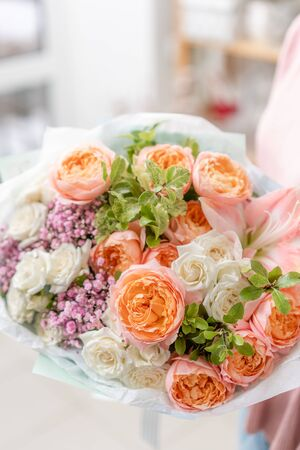 European floral shop. Beautiful bouquet of mixed flowers in womans hands. the work of the florist at a flower shop. Delivery fresh cut flower Stockfoto - 134593128