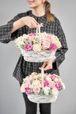 Two Flowers arrangements in Wicker basket. Modern floral shop. Finished work of the florist. Cute bouquet of mixed flowers in womans hands. Delivery fresh cut flower from online store Stockfoto - 134593141