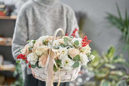 Flower arrangement in Wicker basket. Beautiful bouquet of mixed flowers in woman hand. Floral shop concept . Handsome fresh bouquet. Flowers delivery Stockfoto - 134593144