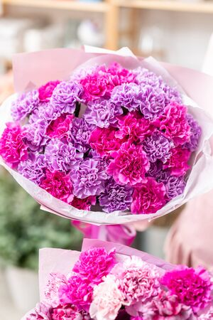 Violet and pink color two mono bouquets of carnation in womans hands. European floral shop. the work of the florist at a flower shop. Delivery fresh cut flower Stockfoto - 134593143