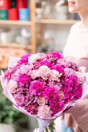 Violet and pink color mono bouquet of carnation in womans hands. European floral shop. the work of the florist at a flower shop. Delivery fresh cut flower Stockfoto - 134593145