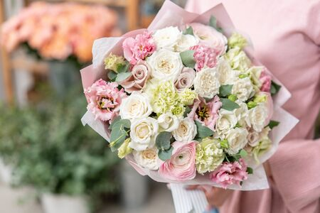 European floral shop. Beautiful bouquet of mixed flowers in womans hands. the work of the florist at a flower shop. Delivery fresh cut flower Stockfoto - 134593148