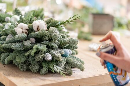 Christmas decor with their own hands. Master class on making decorative ornaments. Flower shop. Woman created a xmas arrangement. Stockfoto