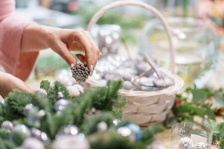 A woman decorates a Christmas arrangement. Hands close-up. Master class on making decorative ornaments. Christmas decor with their own hands. The new year celebration. Flower shop Stockfoto - 134593149
