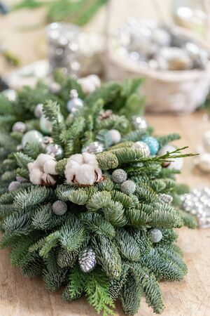 Christmas decor with their own hands. Master class on making decorative ornaments. Flower shop. Woman created a xmas arrangement. Stockfoto - 134593151