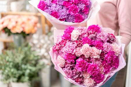 Violet and pink color two mono bouquets of carnation in womans hands. European floral shop. the work of the florist at a flower shop. Delivery fresh cut flower Stockfoto - 134593153