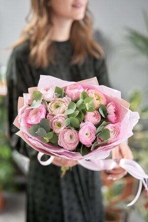 Persian buttercup in womans hands. Bunch pale pink ranunculus flowers with green eucalyptus. The work of the florist at a flower shop Stockfoto - 134593157