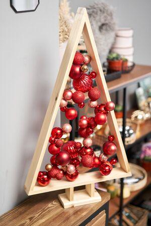 Alternative wooden christmas tree. A handmade Christmas tree and red christmas balls. Stockfoto - 134593158