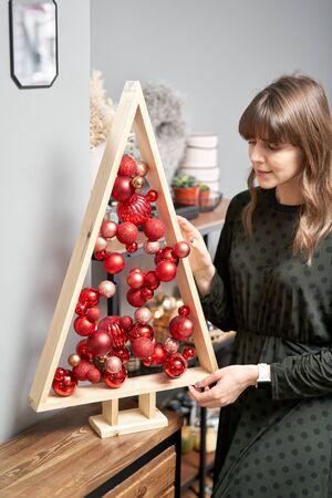 Alternative wooden christmas tree in womans hands . A handmade Christmas tree and red christmas balls. Stockfoto - 134593154