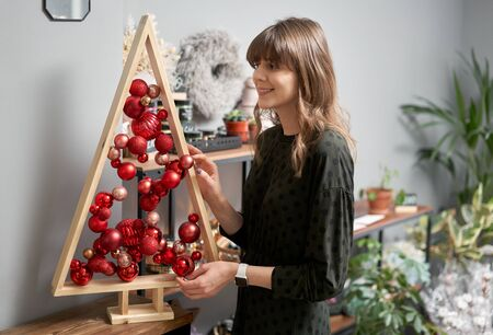 Alternative wooden christmas tree in womans hands . A handmade Christmas tree and red christmas balls. Stockfoto - 134593152