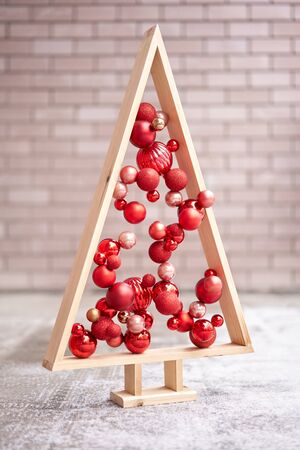 Alternative wooden christmas tree. A handmade Christmas tree and red christmas balls. 免版税图像