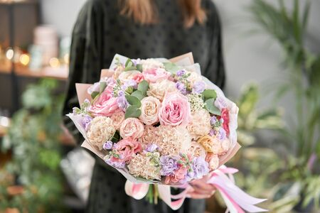 European floral shop. Beautiful bouquet in womans hands. the work of the florist at a flower shop. Delivery fresh cut flower.