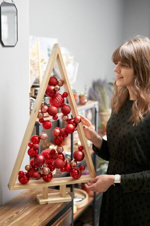 Alternative wooden christmas tree in womans hands . A handmade Christmas tree and red christmas balls.