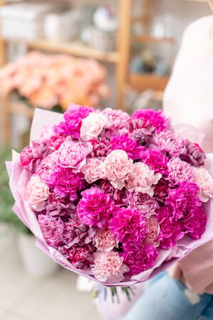 Violet and pink color two mono bouquets of carnation in womans hands. European floral shop. the work of the florist at a flower shop. Delivery fresh cut flower.
