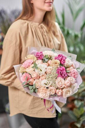 Modern floral shop. Finished work of the florist. Cute bouquet of mixed flowers in womans hands. Delivery fresh cut flower.