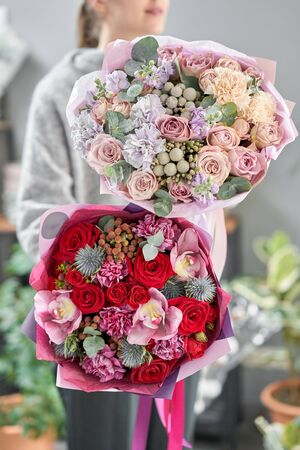 European floral shop. Two Beautiful bouquets of mixed flowers in womans hands. the work of the florist at a flower shop. Delivery fresh cut flower.