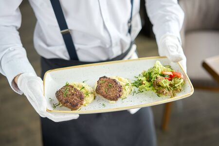 The waiter is holding a plate Delicious juicy meat cutlets, mashed potatoes sprinkled with greens and fresh healthy salad of tomatoes and lettuce leaves Archivio Fotografico