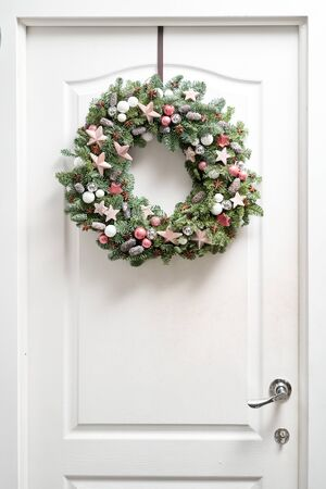 Beautiful Christmas wreath of fresh spruce on the white door. Entrance to the house. Christmas mood. Xmas tree