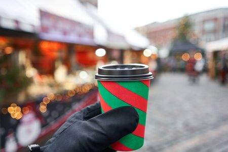 Hand holding a cup of mulled wine with blurred background of winter wonderland, a Christmas Market in European small city.