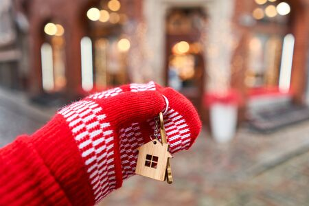 Mortgage or rent concept. Hand in red mitten holding key with house shaped keychain. Real estate, hypothec, moving home or renting property. Christmas mood in blurred background