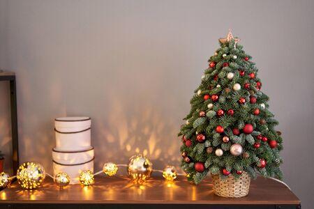 Beau petit sapin de Noël sur table en bois. Bonne humeur. Bokeh de lampe de guirlande sur le fond. Fond d'écran. Pin et sapin du Danemark, Nobilis.