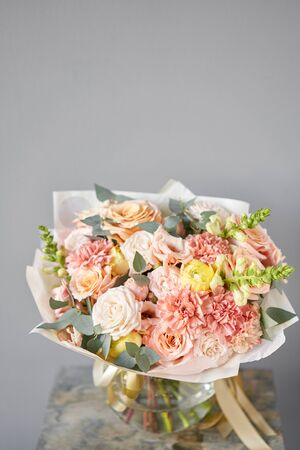 European floral shop. Beautiful bouquet of mixed flowers in glas vase. the work of the florist at a flower shop. Delivery fresh cut flower