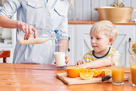 Mother and son are smiling while having a breakfast in kitchen. Mom is pouring milk into glass Archivio Fotografico - 137413061