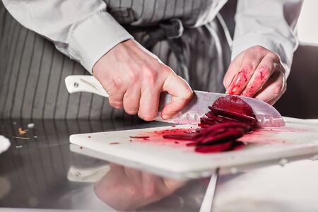 Closeup of hand with knife cutting fresh vegetable. Young chef cutting beet on a white cutting board closeup. Cooking in a restaurant kitchen Stockfoto