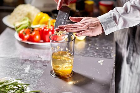 The chef adds garlic. Beating of homemade mayonnaise with olive oil. Mix ingredients for sauce. The chef uses a blender. Step by step sauce preparation Stockfoto