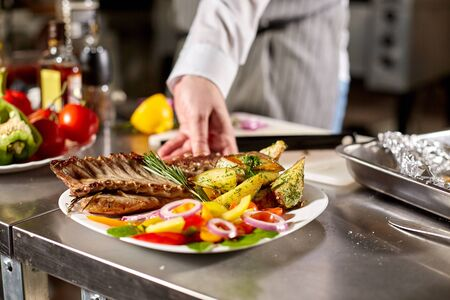 decorated with a sprig of rosemary. the chef prepares in the restaurant. Grilled rack of lamb with fried potatoes and fresh vegetables