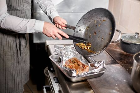 fried ribs of lamb. Cooking with fire in frying pan. Professional chef in a kitchen of restaurant cooking. Man frying food in flaming pan on hob. Stockfoto