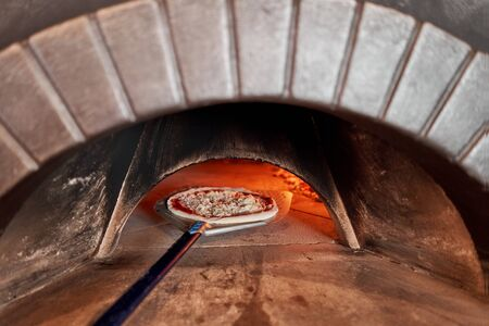 Baked tasty margherita pizza in Traditional wood oven in Naples restaurant, Italy. Original neapolitan pizza. Red hot coal. Stockfoto