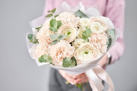 Persian buttercup in womans hands. Bunch pale pink ranunculus flowers with green eucalyptus. The work of the florist at a flower shop Imagens