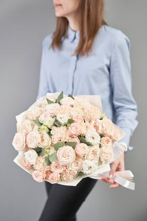 Mono bouquet of spray roses. Delicate bouquet of mixed flowers in womans hands. the work of the florist at a flower shop. Delicate Pastel color. Fresh cut flower. Imagens