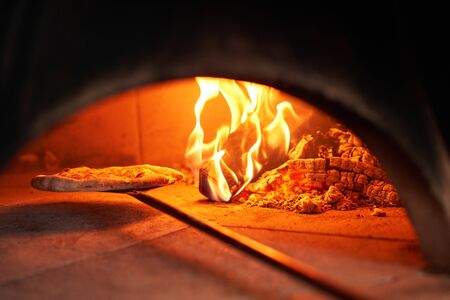 Baked tasty margherita pizza in Traditional wood oven in Naples restaurant, Italy. Original neapolitan pizza. Red hot coal. Imagens