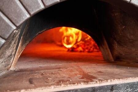 Firewood is burning, the stove is being heated. Red hot coal. Traditional wood oven in Naples restaurant, Italy. Original neapolitan pizza. Stockfoto