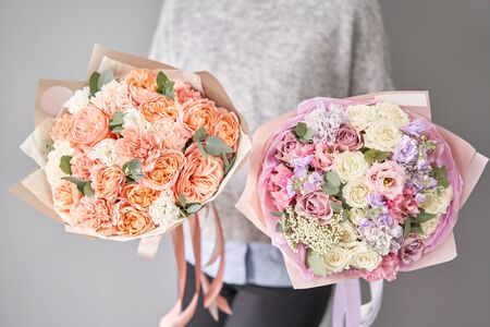 Two Beautiful bouquets of mixed flowers in womans hands. the work of the florist at a flower shop. Delivery fresh cut flower. European floral shop. Imagens